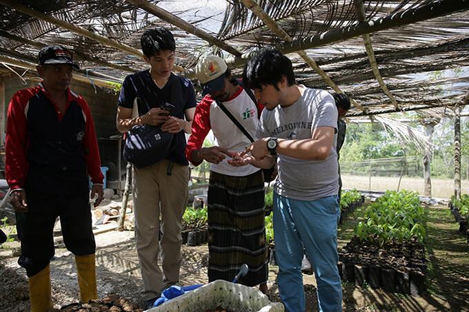 インドネシアでカカオ豆の状態を確かめる吉野慶一社長(写真右)